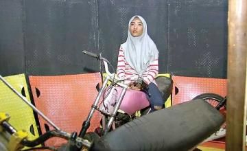 Hijab but no helmet for this Indonesian Wall of Death stunt rider
